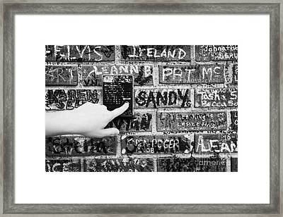Womans Hand Pushing Old Intercom Button On Wall Covered In Graffiti Outside Graceland Memphis Framed Print by Joe Fox
