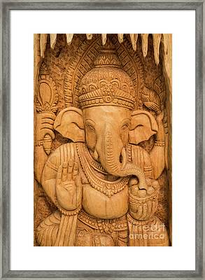 Framed Print featuring the photograph wood carving for Hindu god Ganesha on the wood. by Tosporn Preede