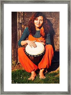 Young Barefoot Lady Drummer Playing On Her Djembe Drum On Rustic Wooden Door Background. Framed Print by Jozef Klopacka