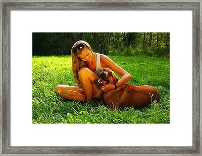 Young Beautiful Woman With Blonde Hair Is Playing With A Mastif Dog In A Backyard With Green Grass Framed Print