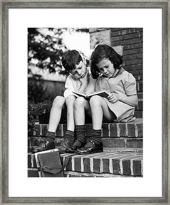 Young Boy & Girl Reading A Book Outdoors Framed Print