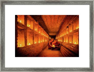 Young Buddhist Monk Are Reading A Book With Light From Candle  Framed Print by Anek Suwannaphoom