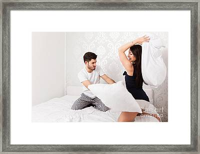 Young Couple Makes A Cushion Fight Framed Print