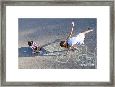 Young Girl Playing Hopscotch On Pavement Framed Print by Bill Bachmann
