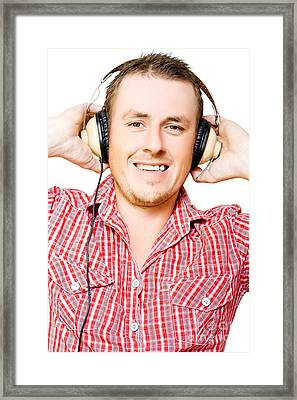 Young Man Listening To Music Through Earphones Framed Print