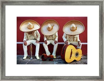 Three Mariachis On An Orange Wall Framed Print