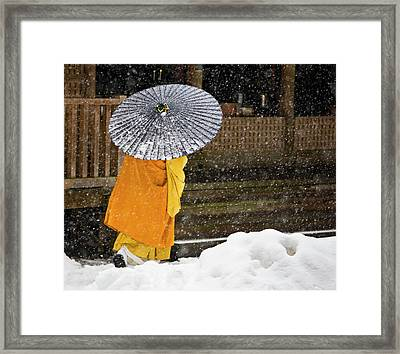 A Buddhist Monk Walks Through A Snow Framed Print by Mint Images - Art Wolfe