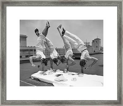 Acrobats Eat While Doing Handstands Framed Print by Bettmann