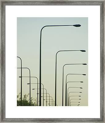 Streetlights Against Afternoon Sky Framed Print by By Ken Ilio