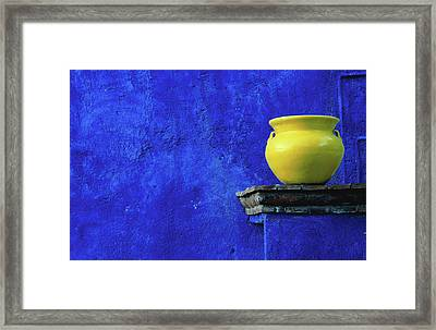 Yellow Pot And Blue Wall Framed Print