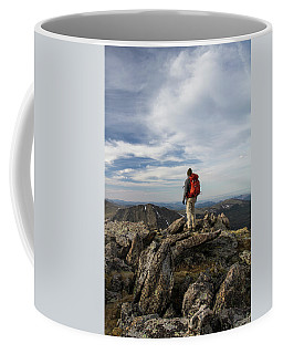 A Backpacker Stands Atop A Dramatic Coffee Mug