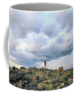 A Backpacker Stands Triumphantly Atop Coffee Mug