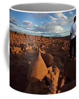 A Man Standing On Rocks Overlooking Coffee Mug