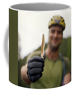 A Man Wearing Bicycle Clothing Holds Coffee Mug