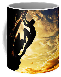 A Silhouette Of Man Free Climbing On Rock Mountain At Sunset Coffee Mug