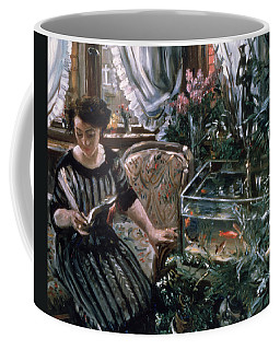 A Woman Reading Near A Goldfish Tank Coffee Mug