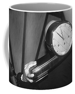 Man Carrying Clock Up Stairs On Coffee Mug
