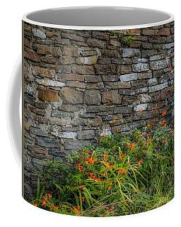 Orange Wildflowers Against Stone Wall Coffee Mug