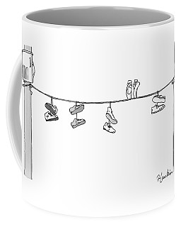 Several Pairs Of Shoes Dangle Over An Electrical Coffee Mug