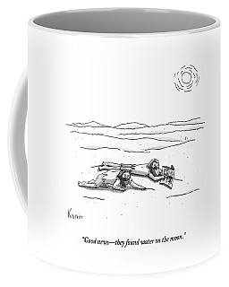 Two Men Are On Their Stomachs In A Desert.  One Coffee Mug
