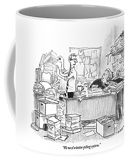 Two People Are In An Office Surrounded By Large Coffee Mug