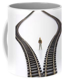 Figurine Between Two Tracks Leading Into Different Directions  Symbolic Image For Making Decisions. Coffee Mug