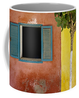 A Tree Outside A Colorful Building And Coffee Mug