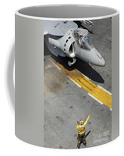 An Airman Uses Hand Signals To Direct Coffee Mug