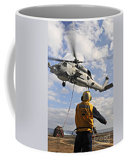 An Sh-60b Sea Hawk Helicopter Releases Coffee Mug
