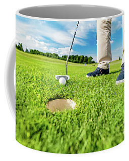 Golfer Putting Ball In The Hole On A Golf Course. Coffee Mug
