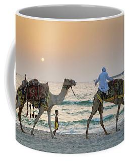 A Little Boy Stares In Amazement At A Camel Riding On Marina Beach In Dubai, United Arab Emirates Coffee Mug