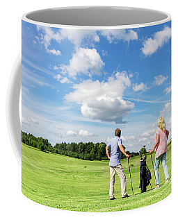 Active Senior Couple Playing Golf On A Course. Coffee Mug