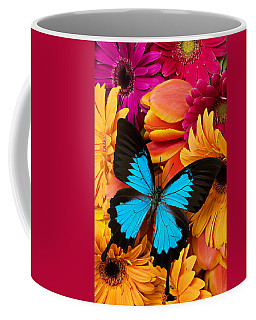 Blue Butterfly On Brightly Colored Flowers Coffee Mug