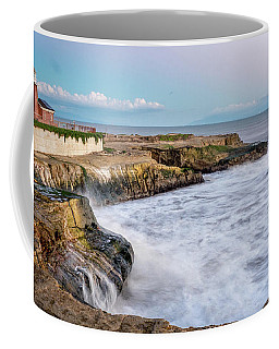Long Exposure Of Waves Against The Cliff With Lighthouse In Shot Coffee Mug
