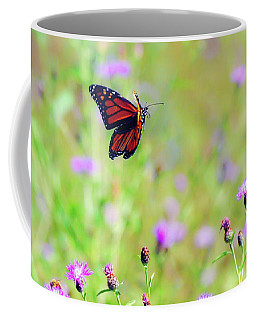 Coffee Mug featuring the photograph Monarch Butterfly In Flight Over The Wildflowers by Kerri Farley