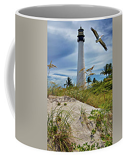 Coffee Mug featuring the photograph Pelican Flying Over Cape Florida Lighthouse by Justin Kelefas