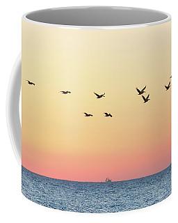 A Dozen Pelicans Flying Over The Ocean Coffee Mug by Robert Loe