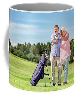 Senior Couple Giving Thumbs Up On A Golf Course. Coffee Mug