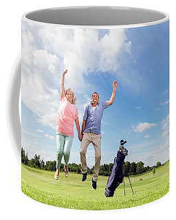 Senior Couple Jumping On A Golf Course. Coffee Mug