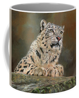 Snow Leopard On Rock Coffee Mug by David Stribbling