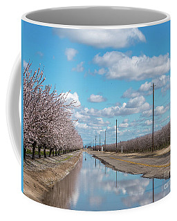 Coffee Mug featuring the photograph White Clouds And Blue Skies Reflected On Large Puddle On Farm Ro by PorqueNo Studios