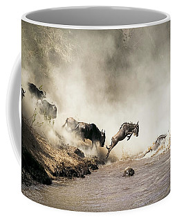Wildebeest Leaping In Mid-air Over Mara River Coffee Mug