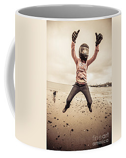 Woman Wearing Helmet And Gloves Jumping On Beach Coffee Mug