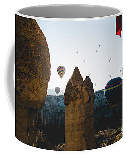 hot air balloons for tourists flying over rock formations at sunrise in the valley of Cappadocia. Coffee Mug