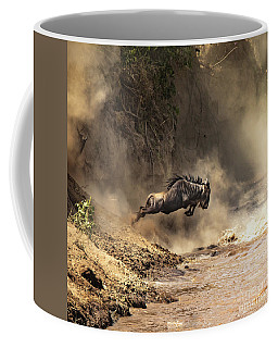 Wildebeest Leaps From The Bank Of The Mara River Coffee Mug