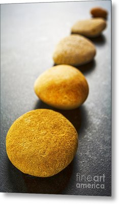 Diagonal Line Of Brown Pebbles On Dark Background Metal Print