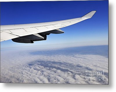 Wing Of Flying Airplane Above Clouds Metal Print
