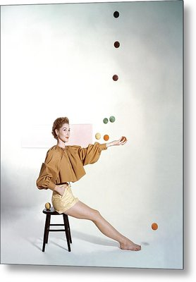 A Model Sitting On A Stool Juggling Metal Print by John Rawlings
