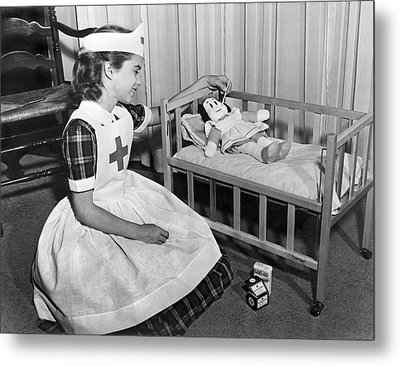 A Young Girl Plays Nurse To Her Little Lulu Doll. Metal Print by Underwood Archives