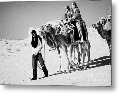 bedouin guide in modern clothing leads british tourists riding camels and wearing desert clothes into the sahara desert at Douz Tunisia Metal Print by Joe Fox